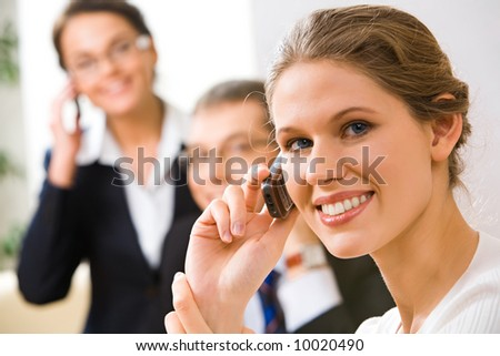 Portrait of beautiful business woman talking with people on her mobile phone - stock photo