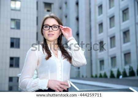 Portrait of beautiful business woman wearing glasses and hold smart phone. - stock photo