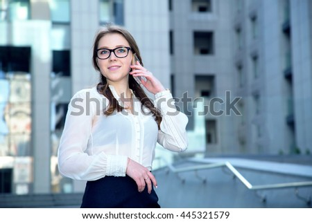 Portrait of beautiful business woman wearing glasses and talking on a mobile phone. - stock photo