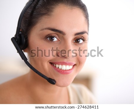 Portrait of beautiful business woman working at her desk with headset and laptop. - stock photo