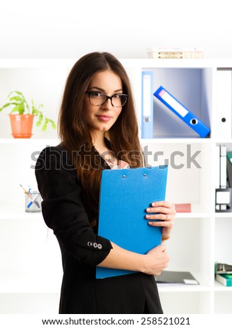 Portrait of beautiful businessperson standing with document file at her workplace. Young friendly real estate agent wearing eyeglasses working in the office.   - stock photo