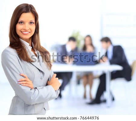 portrait of beautiful businesswoman in office with colleagues - stock photo