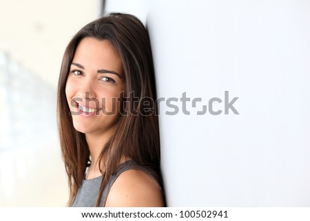 Portrait of beautiful businesswoman leaning against wall - stock photo