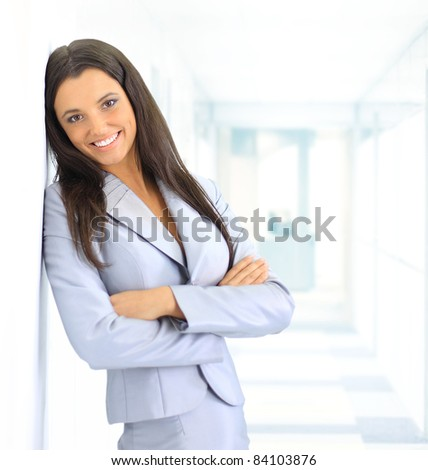 portrait of beautiful businesswoman leaning against white wall in office - stock photo