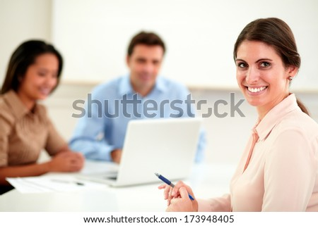 Portrait of beautiful businesswoman looking and smiling at you while working with her team on office