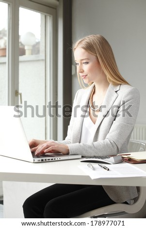 Portrait of beautiful businesswoman sitting at desk and working in office. - stock photo