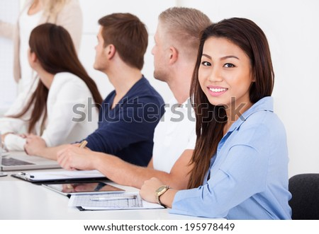 Portrait of beautiful businesswoman sitting with colleagues in meeting at office - stock photo