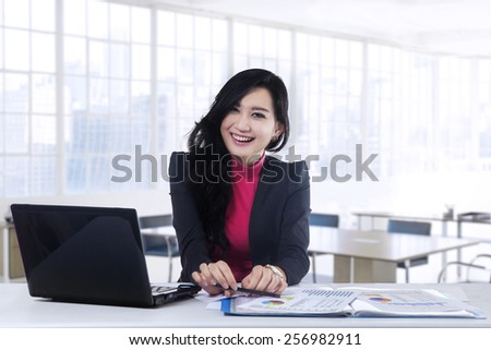 Portrait of beautiful businesswoman smiling at the camera while working with laptop on desk in the office - stock photo