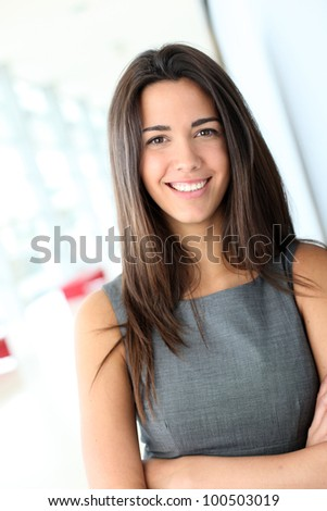 Portrait of beautiful businesswoman standing in hall - stock photo