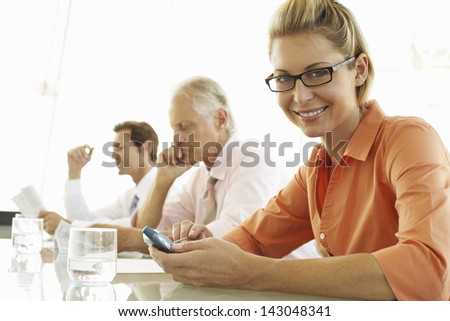 Portrait of beautiful businesswoman using cell phone with colleagues in conference room - stock photo