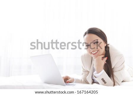 Portrait of beautiful businesswoman using laptop in hotel - stock photo