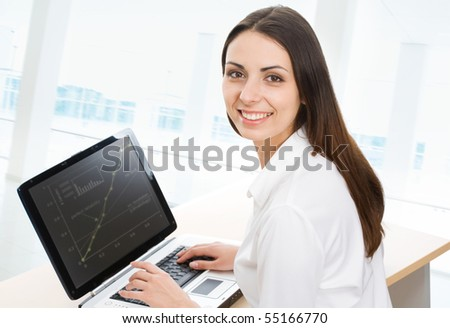 Portrait of beautiful businesswoman while typing on the laptop - stock photo