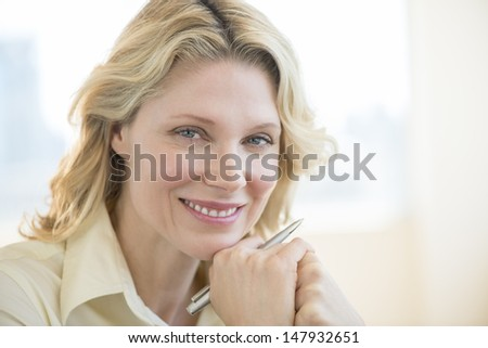 Portrait of beautiful businesswoman with hand on chin smiling in office - stock photo