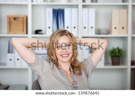 Portrait of beautiful businesswoman with hands behind head in office - stock photo