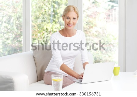Portrait of beautiful businesswoman with laptop sitting at home and working online.