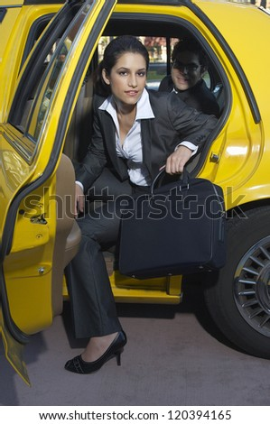 Portrait of beautiful businesswoman with male colleague getting out of taxi - stock photo