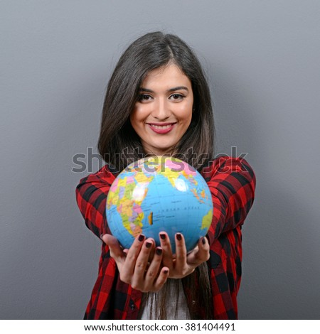 Portrait of beautiful casual woman holding globe against gray background - stock photo