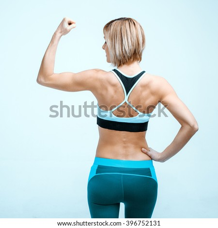 Portrait of beautiful caucasian blonde sporty woman. Young athlete showing strong arm and back - stock photo