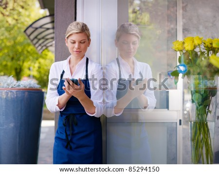 Portrait of beautiful caucasian girl self-employed in flower shop, smiling and using mobile phone. Horizontal shape, waist up