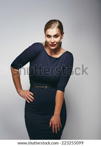 Portrait of beautiful caucasian plus size model in black dress.  - stock photo