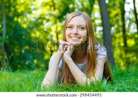 Portrait of beautiful caucasian smiling red-haired young woman, against summer green park. - stock photo
