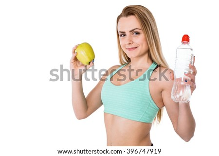 Portrait of beautiful caucasian sporty woman. Young athlete smiling, holding green apple and bottle of water, looking at camera. Isolated on white background - stock photo