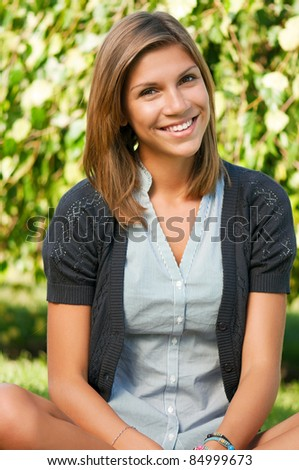 Portrait of beautiful caucasian teenager girl in park outdoors - stock photo
