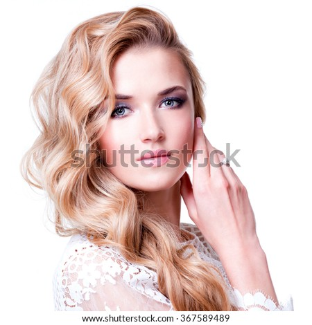 Portrait of beautiful caucasian woman with blond curly hair posing at studio. - stock photo