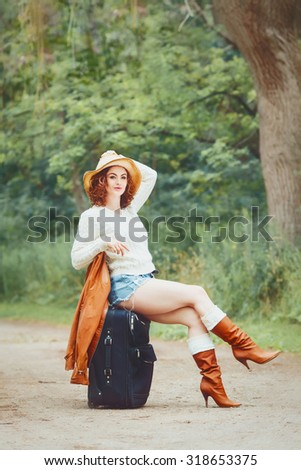 Portrait of beautiful Caucasian young girl woman in white sweater, high leather brown boots, blue denim shorts, straw hat, sitting on travel bag on the country road, wanderlust adventure vacation  - stock photo
