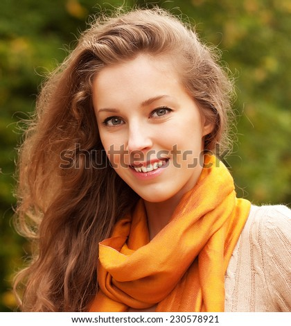 Portrait of beautiful charming smiling woman in autumn park - stock photo