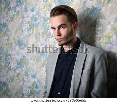 Portrait of beautiful charming young man with blue eyes and fair hair over floral background - stock photo