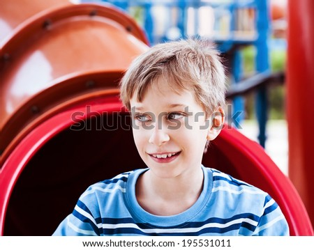 Portrait of beautiful cheerful child playing on a playground in summer looking excited  - stock photo