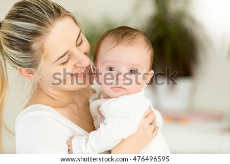 Portrait of beautiful cheerful mother embracing her 3 months old baby boy