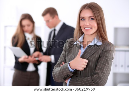 Portrait of beautiful cheerful smiling business woman showing ok on the background of business people Successful business concept - stock photo