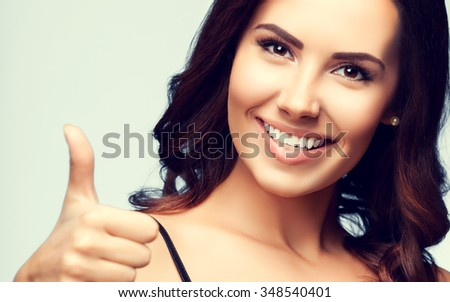 Portrait of beautiful cheerful smiling woman showing thumb up hand sign gesture - stock photo