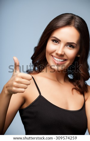 Portrait of beautiful cheerful smiling woman showing thumb up hand sign gesture, over grey background - stock photo