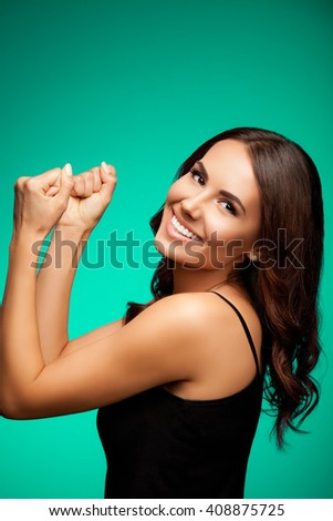 Portrait of beautiful cheerful smiling young woman happy gesturing, over bright green background - stock photo