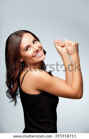 Portrait of beautiful cheerful smiling young woman happy gesturing, over bright grey background - stock photo
