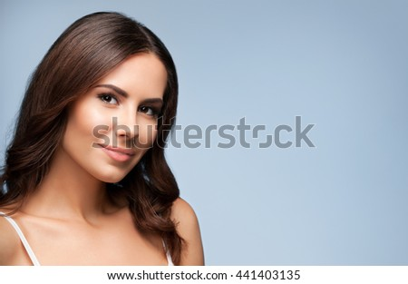 Portrait of beautiful cheerful smiling young woman, on grey background, with blank copyspace area for text or slogan - stock photo
