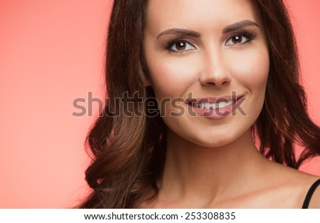 Portrait of beautiful cheerful smiling young woman, on red background - stock photo