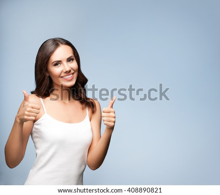 Portrait of beautiful cheerful smiling young woman showing thumb up gesture, on grey background, with blank copyspace area for text or slogan - stock photo
