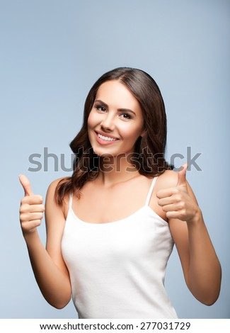 Portrait of beautiful cheerful smiling young woman showing thumb up gesture, on grey, with blank copyspace area for text or slogan - stock photo