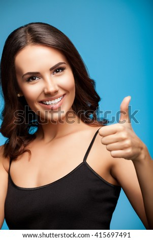 Portrait of beautiful cheerful smiling young woman showing thumb up hand sign gesture, over blue background - stock photo