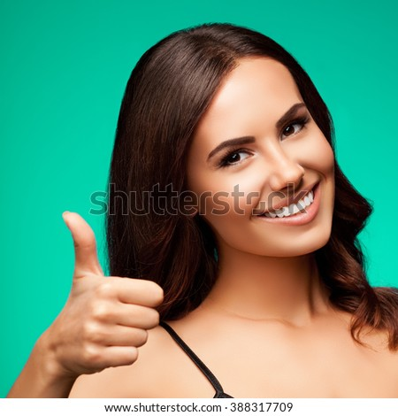 Portrait of beautiful cheerful smiling young woman showing thumb up hand sign gesture, over green background - stock photo