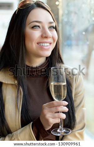Portrait of beautiful cheerful woman with a glass of champagne. Isolated on white - stock photo