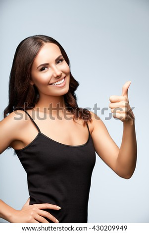 Portrait of beautiful cheerful young woman showing thumb up hand sign gesture, over bright grey background - stock photo