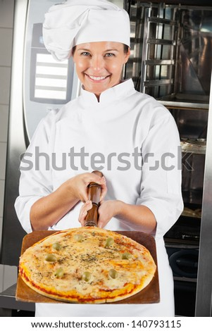 Portrait of beautiful chef presenting pizza at commercial kitchen