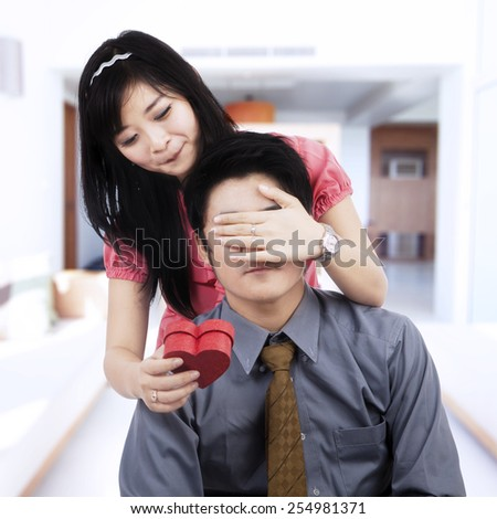 Portrait of beautiful chinese woman closing her husband eyes while giving a gift at home - stock photo