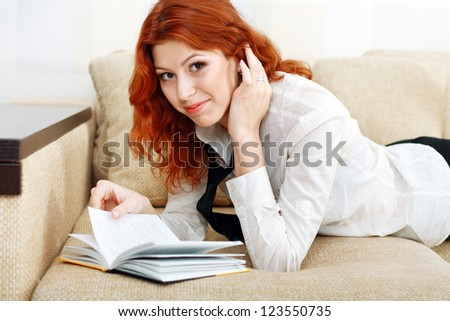 Portrait of beautiful college girl relaxing on sofa with book