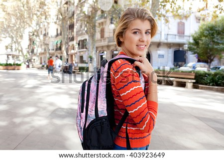 Portrait of beautiful college student in a city avenue with trees and stone pavement, carrying a backpack, turning and smiling at camera, outdoors. Student lifestyle, sunny street exterior. - stock photo